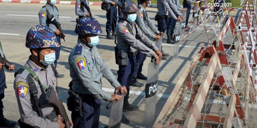 Burmese police stand guard at a checkpoint in Yangon.