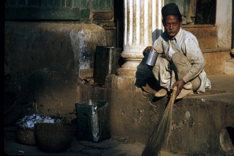 A dalit sweeper at Pharping Boarding School takes a tea break. During this period in the morning, everyone was served tea in ceramic tea cups, except for this worker, who, because of his caste, was given his tea in an empty tin can. Dakshinkali, Kathmandu 1963 Photo credit: Jim Fisher