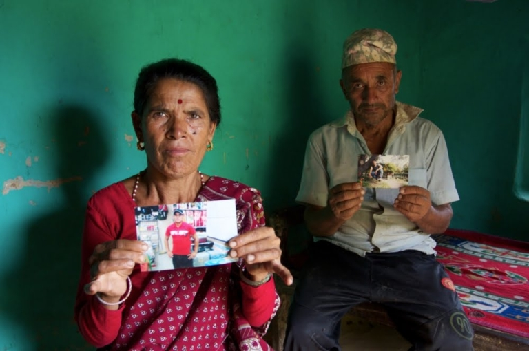 Dalli Khatri and her husband Lil Man, hold photos of their sons, both of whom died while working as migrants in Malaysia and Qatar. Their younger son (foreground photo) died in Qatar from a heart attack, aged 20.