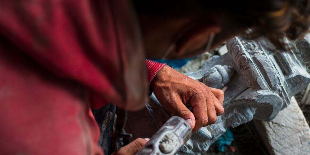 A worker at Bajracharya's workshop carving the Pancha Buddha.